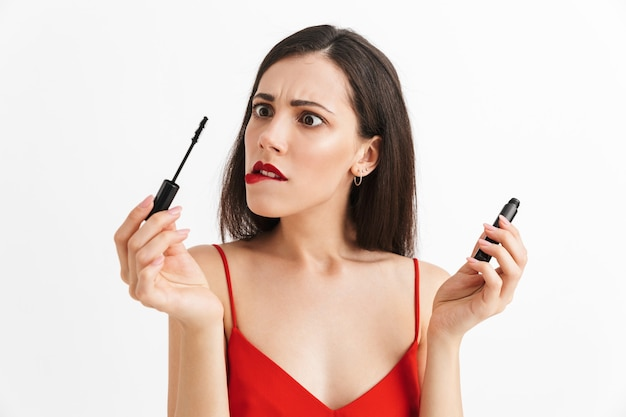 Photo of young nervous beautiful woman posing isolated holding lip gloss doing makeup.