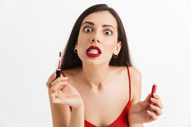 Photo of young nervous woman posing isolated holding lip gloss doing makeup.