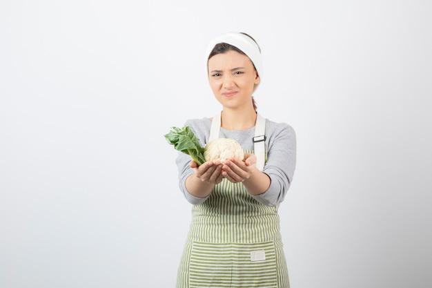 Foto di una giovane e simpatica modella in grembiule con in mano un cavolfiore