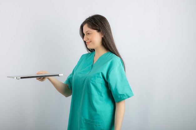 Photo of young nurse giving away her laptop on white.