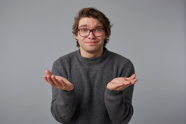 Photo of young pleaseful man with glasses wears in gray sweater, stands over gray background, and spreads his palms to the side.