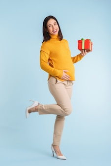 Photo of a young pregnant woman isolated holding gift box.