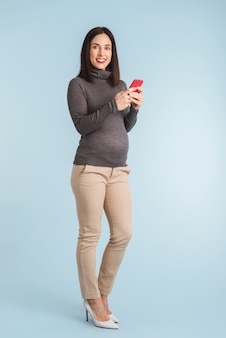 Photo of a young pregnant woman isolated using mobile phone.