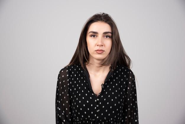 Foto di giovane donna seria in piedi e in posa.