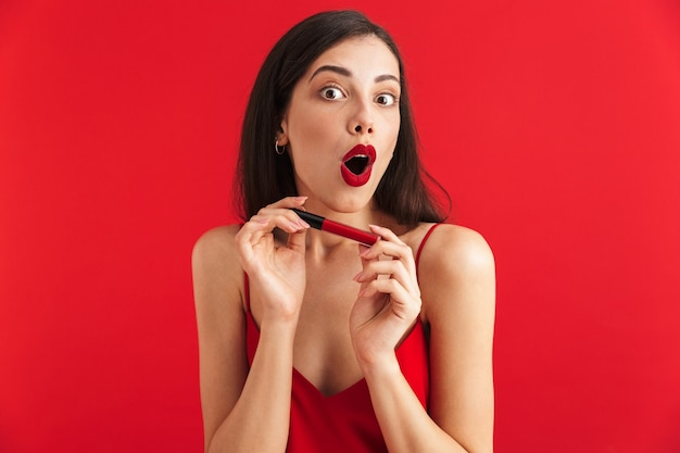 Photo of young shocked excited woman posing isolated holding lip gloss doing makeup.