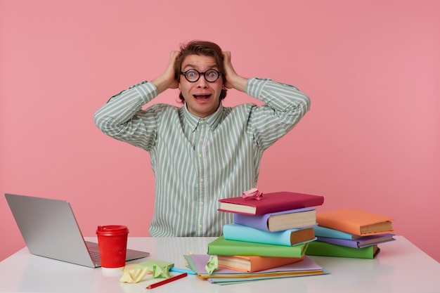 Photo of young shocked guy in glasses, sits by the table and working with laptop, holds his head and looks surprised and scared , isolated over pink background.