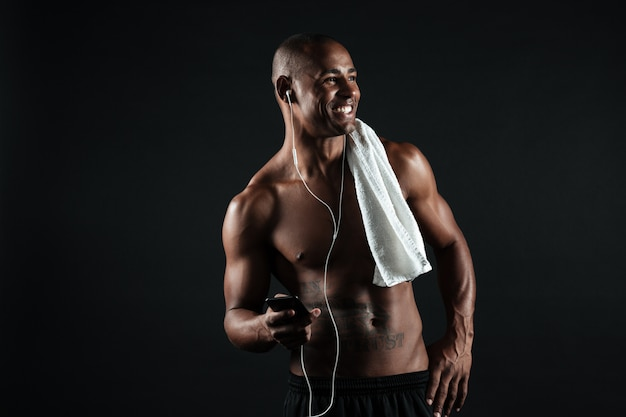 Photo of young smiling afro american sports man with towel holding phone and listen to music