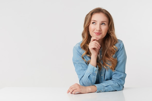 Photo of young smiling blonde woman wears in denim shirts, sitting at the white table and touches chin, dreaming and looks happy, isolated over white background.