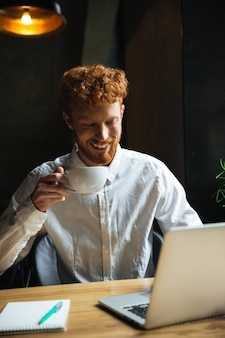 Photo of young smiling redhead bearded man holding coffee cup, looking at laptop screen while working at cafeteria
