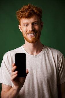 Photo of young smiling redhead bearded man in white tshirt makes a photo on smartphone mobile