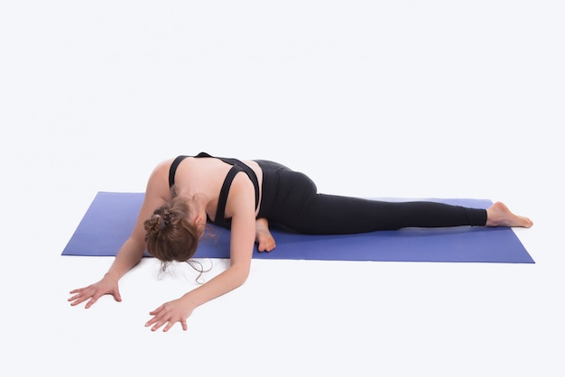 Photo of young sport woman doing yoga on mat over white space in studio