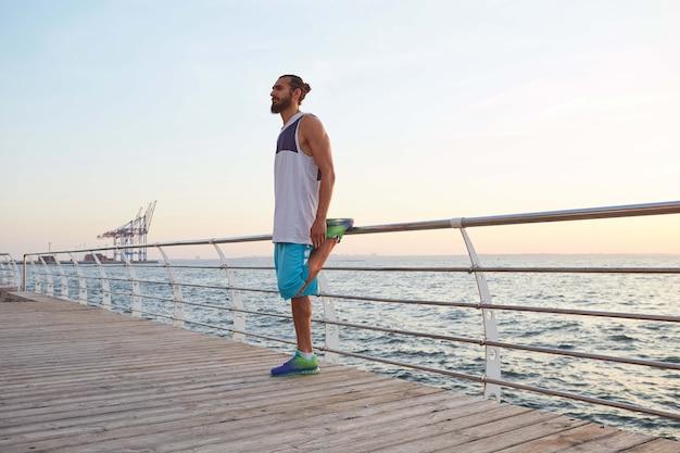 Foto di giovane uomo barbuto sportivo in riva al mare che fa un riscaldamento prima di una corsa mattutina, distoglie lo sguardo.