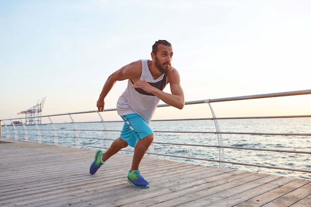 Photo of young sporty bearded running guy at the seaside, looks good.