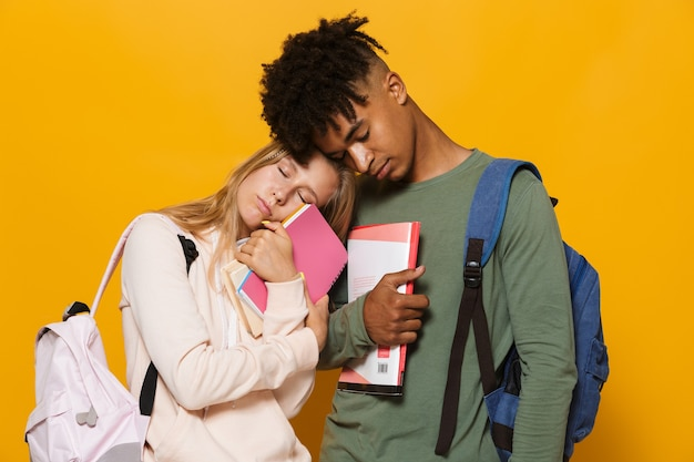 Photo of young students guy and girl 16-18 wearing backpacks sleeping together while holding exercise books, isolated over yellow background