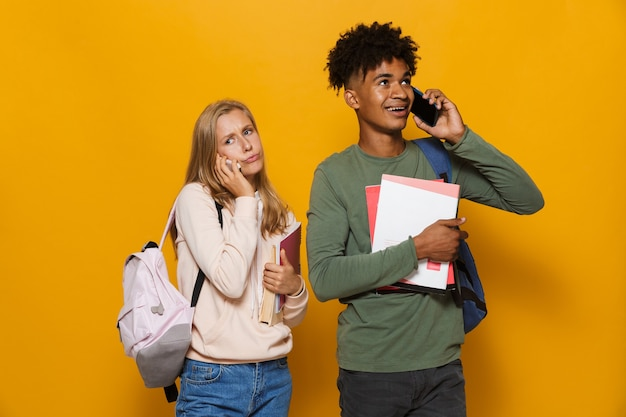 Photo of young students man and woman 16-18 wearing backpacks talking on mobile phones and holding exercise books, isolated over yellow background