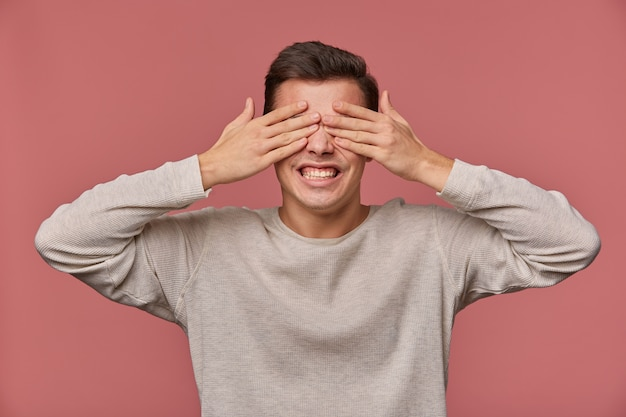 Photo of young surprised guy in blank long sleeve covers eyes with palms, stands over pink background with wide open eyes and screaming.