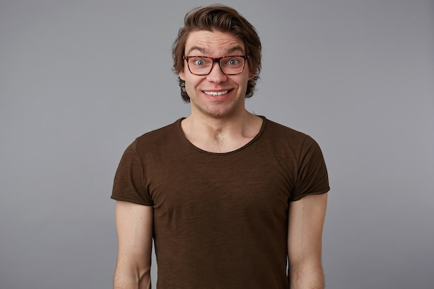 La foto del giovane uomo bello sorpreso con gli occhiali indossa magliette di base, si erge su uno sfondo grigio e sorride in generale, sembra felice e meravigliata. Foto Gratuite
