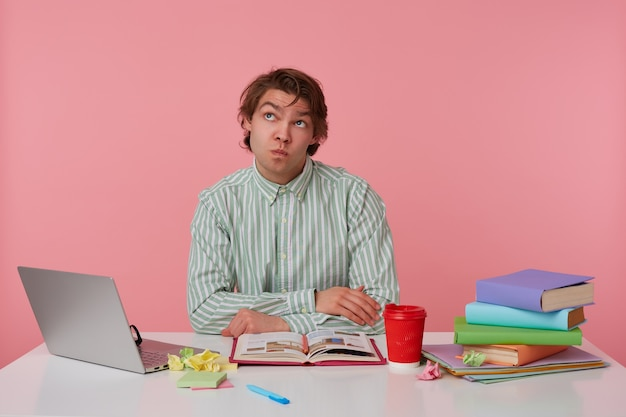 Photo of young thinking guy with glasses, sitting at a table with books, working at a laptop, wishful looks up, isolated over pink background.