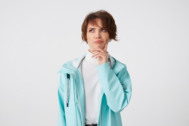 Photo of young thinking short-haired lady in white golf and light blue rain coat, touches cheek and frowning looks up, stands over white background.