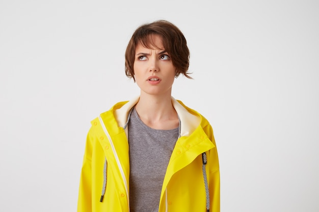 Photo of young thinking short-haired lady in yellow rain coat, looks discontent and doubting, frowning looks up at the left side, stands over white background.