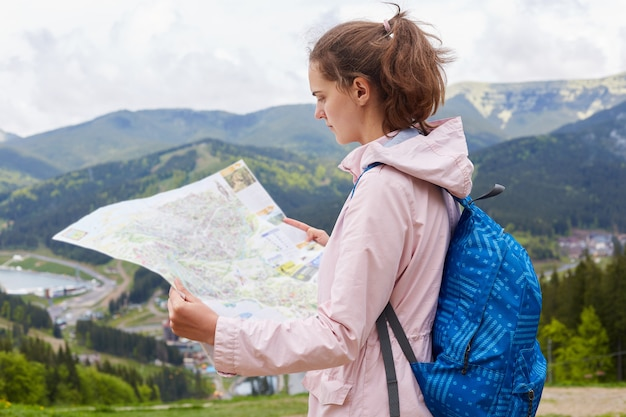 Photo of young traveler woman find way direction with map in hand, lady posing against beautiful landscape being on top of mountain