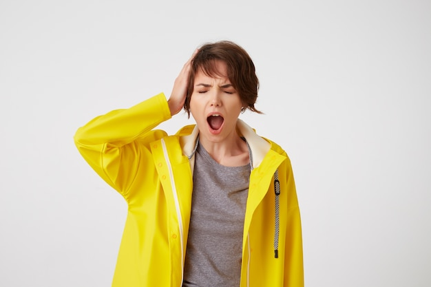 Photo of young unhappy short-haired lady in yellow rain coat, holding shes head, feeling strong migraine, frowning and screaming, stands over white background.