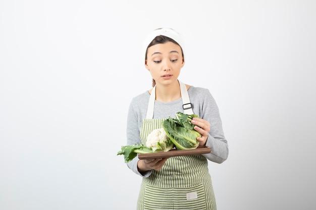 Foto di una giovane donna in grembiule che tiene un piatto di legno con cavolfiori