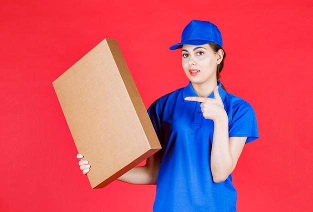 Foto della giovane donna in attrezzatura blu che indica la scatola di cartone sopra la parete rossa.