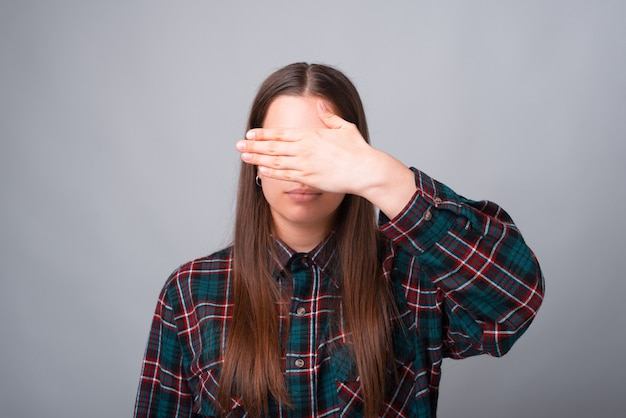 Photo of young woman covering her face with palm
