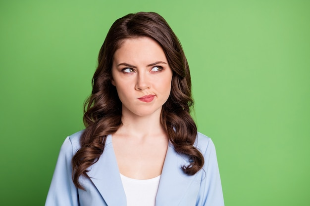 Photo of young woman curly hairdo look up empty space wear blue blazer isolated green color background