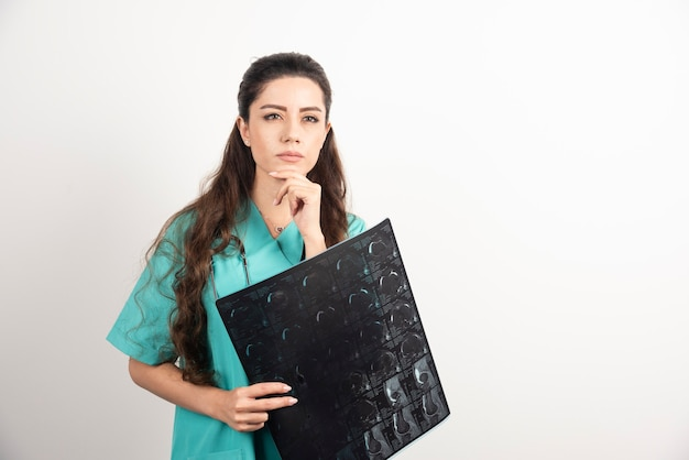 Photo of a young woman doctor holding x-ray over white wall.