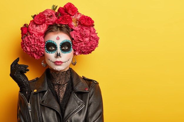 Photo of young woman has face arfully painted to resemble skulls, wears black leather jacket and gloves, wears garland made of red aromatic flowers