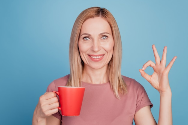 Photo of young woman hold mug of coffee show okay alright perfect sign isolated over blue color background