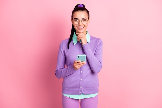 Photo of young woman hold telephone arm finger chin wear spectacles purple cardigan isolated pink color background