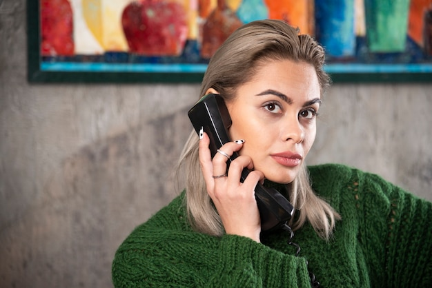 Photo of young woman holding a black telephone