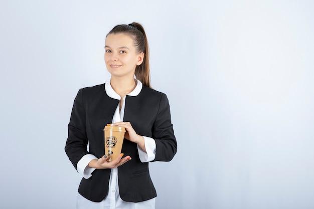 Foto della giovane donna che tiene tazza di caffè su bianco.