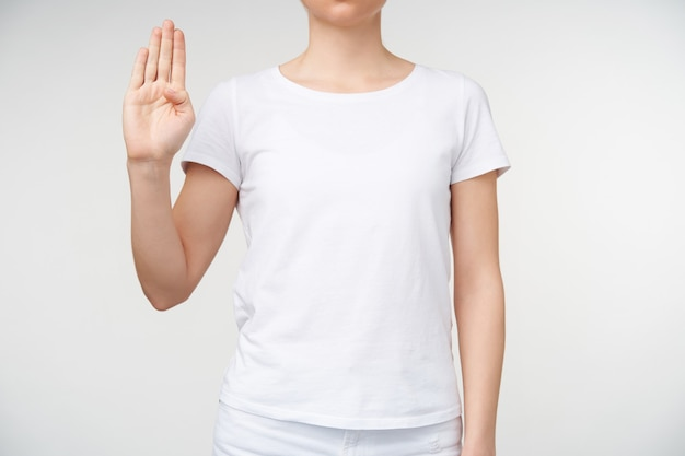 Photo of young woman learning deaf alphabet and forming letter b with raised hand, being isolated over white background in white basic t-shirt