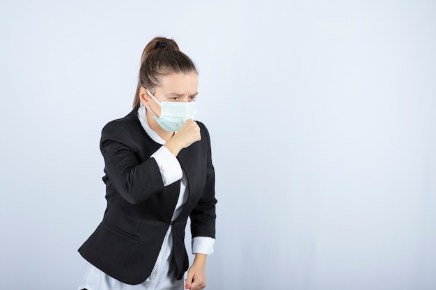 Photo of young woman in mask coughing on white background. high quality photo