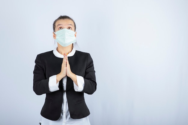Foto di giovane donna in maschera che prega su priorità bassa bianca. foto di alta qualità