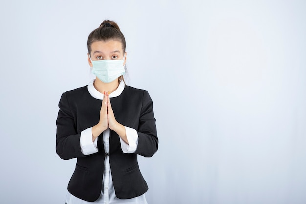 Photo of young woman in mask praying on white background. high quality photo