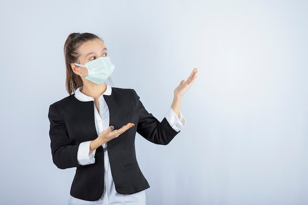 Photo of young woman in mask showing something on white background. high quality photo