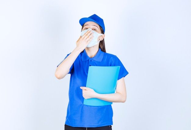 Photo of young woman in medical mask holding folder and yawning.