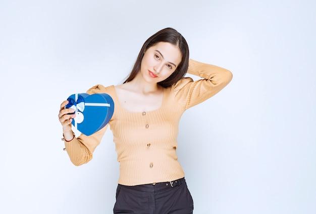 Foto di una modella di giovane donna che tiene una confezione regalo blu contro il muro bianco.