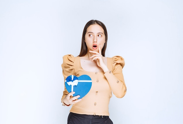 Photo of a young woman model holding a heart shaped gift box against white wall.