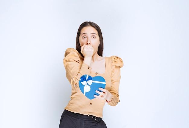 Foto di una modella di giovane donna che tiene una confezione regalo a forma di cuore contro il muro bianco.