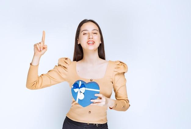 Foto di una modella di giovane donna con una confezione regalo a forma di cuore rivolta verso l'alto.