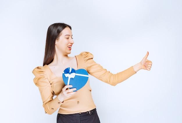 Foto di una modella di giovane donna con una confezione regalo a forma di cuore che mostra un pollice in su.
