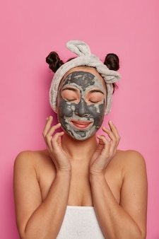 Photo of young woman relaxes with facial mask, touches her fresh skin, enjoys beauty treatments, stands wrapped in towel, closes eyes, models against pink wall, cares about complexion.