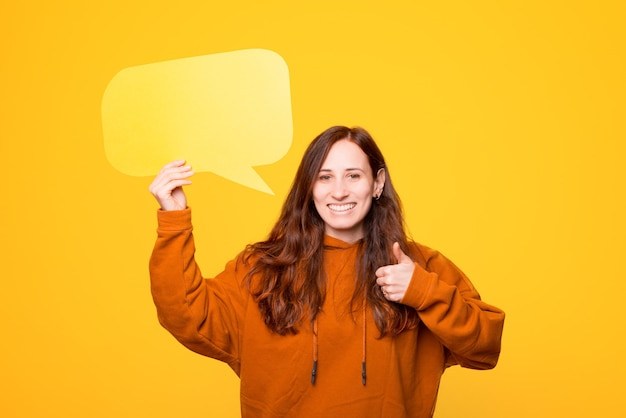 Photo of a young woman that is holding a speech bubble showing a thumb up is smiling