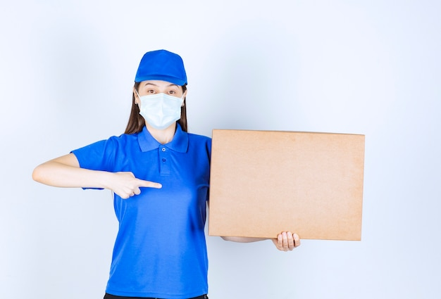 Photo of young woman in uniform and medical mask pointing at paper box .